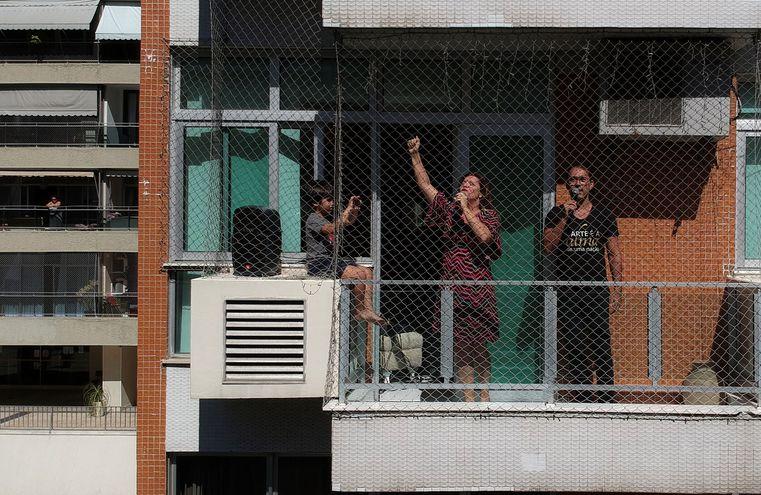 Una pareja de cantantes de ópera del Teatro Municipal convirtió la ventana del apartamento en el que viven en un escenario para cantarle a sus vecinos y darles algunos minutos de alegría en tiempos de confinamiento por la pandemia del coronavirus, en Río de Janeiro (Brasil).