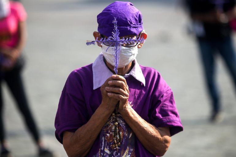 Un hombre con mascarilla reza durante una procesión religiosa en Caracas, Venezuela.