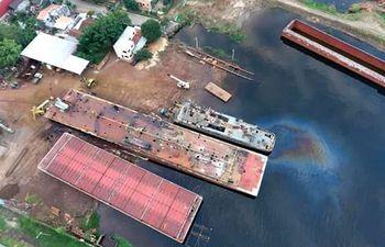 Se puede ver la mancha del hidrocarburo en el agua, donde los operarios del astillero del diputado Bachi Núñez y su mujer limpian, reparan y desguazan embarcaciones.