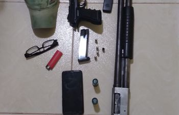 Las armas, cartuchos, celulares y otros objetos incautados.