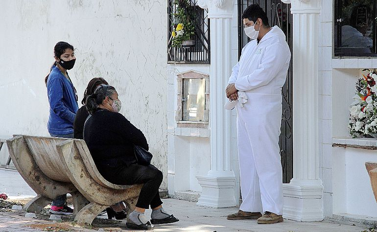 Un ciudadano boliviano, con  traje blanco de bioseguridad, reza con familiares de un fallecido por covid-19 en Santa Cruz. (EFE)