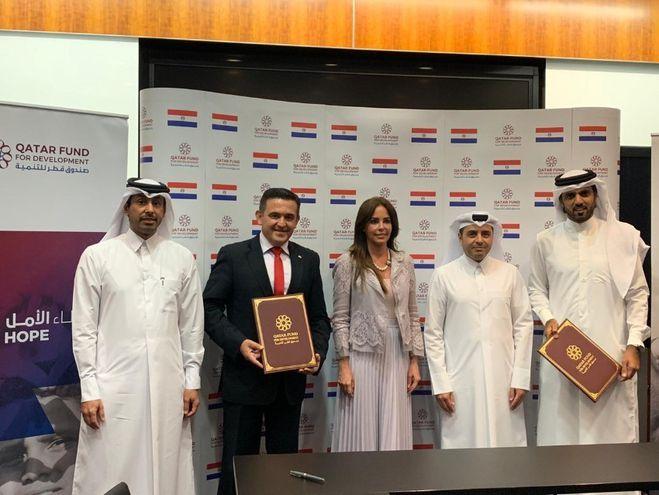 Autoridades nacionales junto con las de Qatar, firmando el acuerdo.