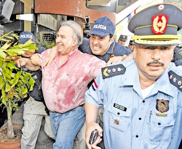 El exsenador Óscar González Daher se ríe, tras ser rociado con agua, cuando concurrió a la sede judicial para responder por las acusaciones por enriquecimiento ilícito y tráfico de influencias cuando presidía el Jurado de Enjuiciamiento de Magistrados.