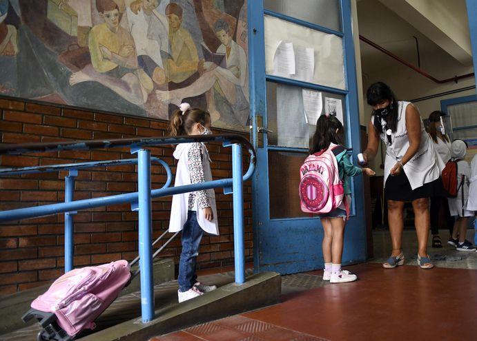 Alumnas de un colegio de Buenos Aires hace fila para que se les tome la temperatura antes de entrar a clases.