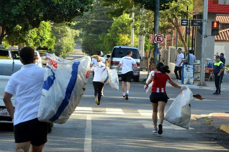 """Jóvenes y adultos corrieron ayer en el """"Asunción Plogging 2020"""". La carrera consistió en recoger residuos mientras se corría y luego depositarlos en los recolectores de basura de la Comuna asuncena."""