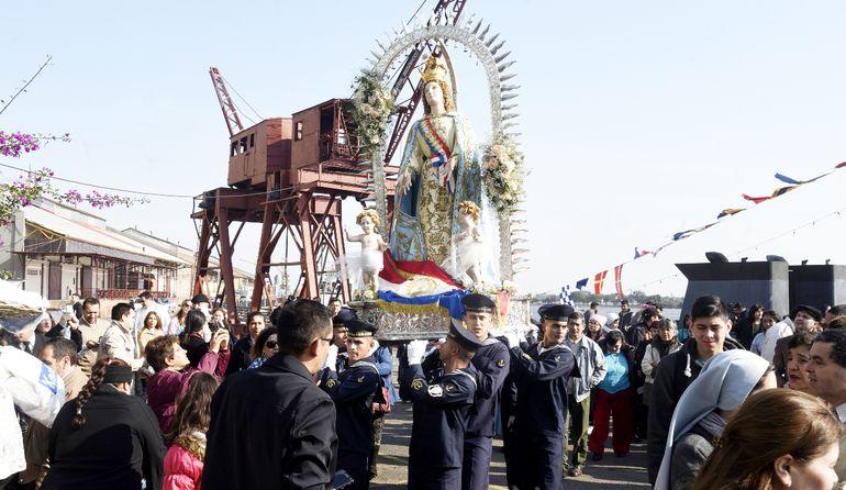 La imagen de la Virgen de la Asunción es portada por  marineros a poco de ser bajada de una embarcación en que recorrió el río Paraguay.