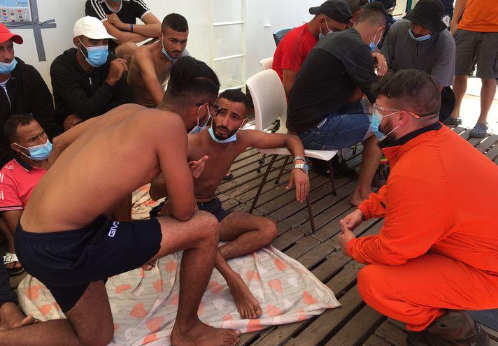 """Un rescatista habla con migrantes en el barco """"Ocean Viking"""", luego de que dos de ellos saltaran por la borda en el mar Mediterráneo y fueran rescatados."""