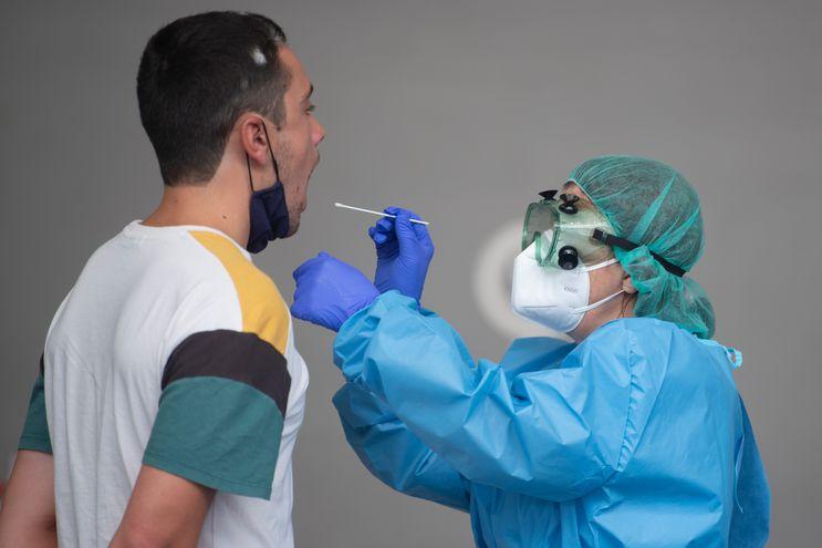 Un trabajador de la salud usa un hisopo para recolectar una muestra de un hombre en un centro de pruebas temporal para el nuevo coronavirus en la ciudad vasca española de Azpeitia.