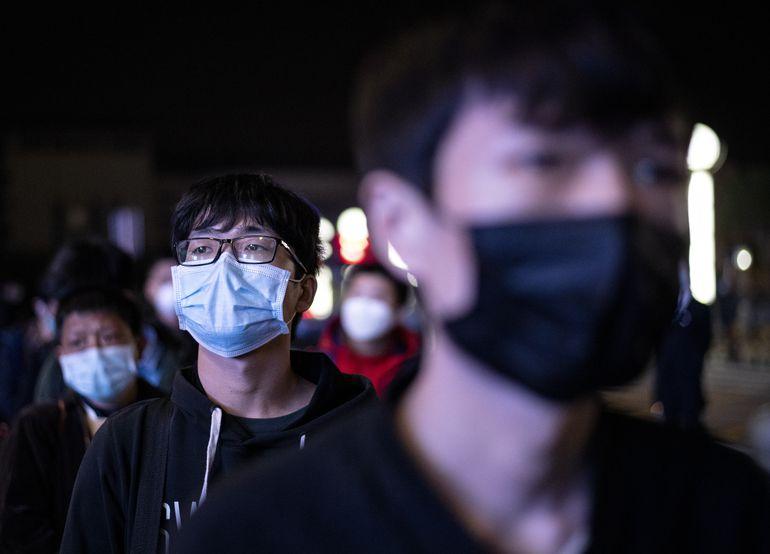Pasajeros con mascarillas hacen fila en una estación de trenes en Wuhan, China.