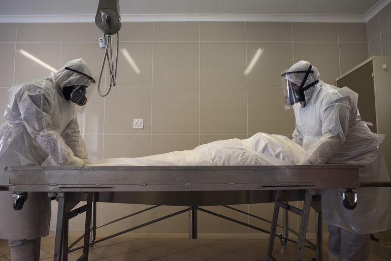 Funcionarios de una funeraria musulmana preparan el cuerpo de un hombre fallecido por COVID-19 para su entierro en la mezquita Ghietmatiel Islamia en Ciudad del Cabo, Sudáfrica.