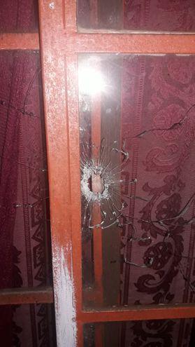Uno de los disparos impactó en el vidrio de la puerta de la vivienda.