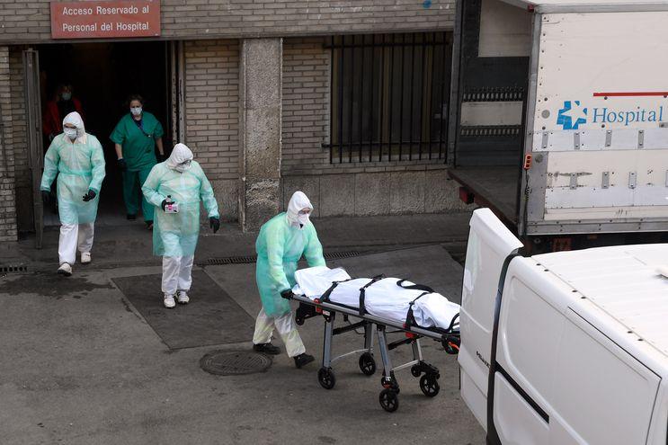 Un trabajador de la salud lleva un cuerpo en una camilla frente al hospital Gregorio Maranon en Madrid el 25 de marzo de 2020.