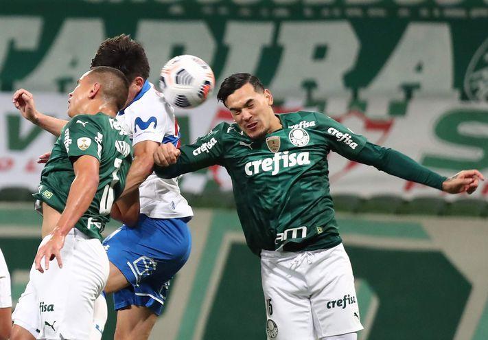Gustavo Gómez (d), de Palmeiras, salta en procura del balón ante un jugador de Universidad Católica.