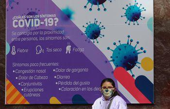 Una mujer espera frente a un cartel con información sobre COVID-19 a tres meses de la cuarentena decretada por la pandemia de COVID-19, en La Paz (Bolivia).