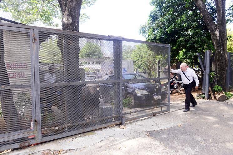 Una persona  empuja el pesado portón que debía abrirse automáticamente con la llegada de cada concejal.