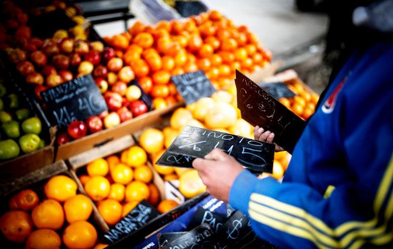 Un empleado de un mercado callejero de frutas y verduras cambia  los precios de los productos como consecuencia de la devaluación del peso en los últimos días.