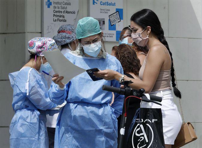 Una enfermera comprueba la cita previa de una mujer en la puerta del Centro de Atención Primaria del barrio de la Florida de L'Hospitalet (Barcelona).