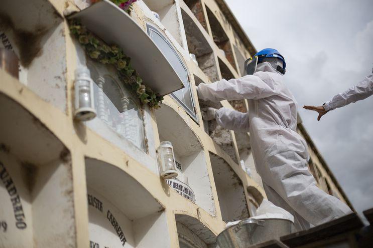 Trabajadores de un cementerio en Huanuco, Perú, cargan un féretro a un nicho.