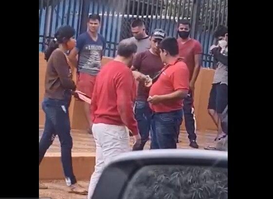 Un sospechoso hombre vestido de rojo repartiendo billetes frente a un local de votación de Asunción.