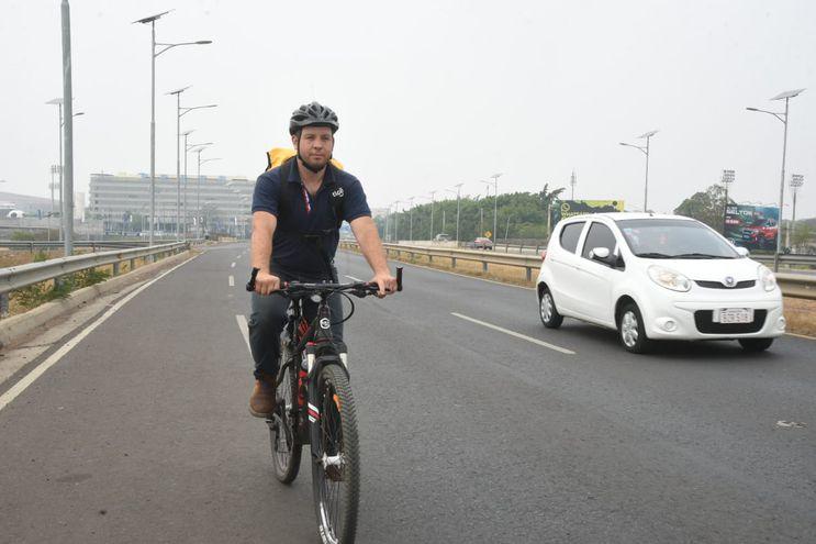 Un ciclista circula por la avenida Ñu Guasu y comparte el espacio con otros vehículos a motor.