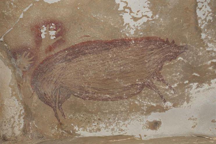 La imagen de un jabalí y dos huellas de manos conforman la pintura hallada en Indonesia.