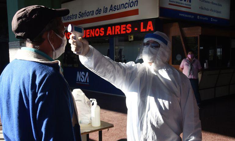 Funcionarios toman la temperatura a todos los pasajeros que ingresan a la Terminal de Ómnibus de Asunción.