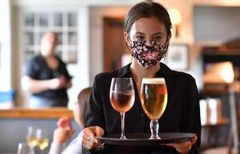 Una mujer que atiende en el pub y restaurante The Shy Horse en Chessington, Gran Londres, durante el primer día de una mayor relajación de las restricciones de bloqueo durante la nueva pandemia de COVID-19.