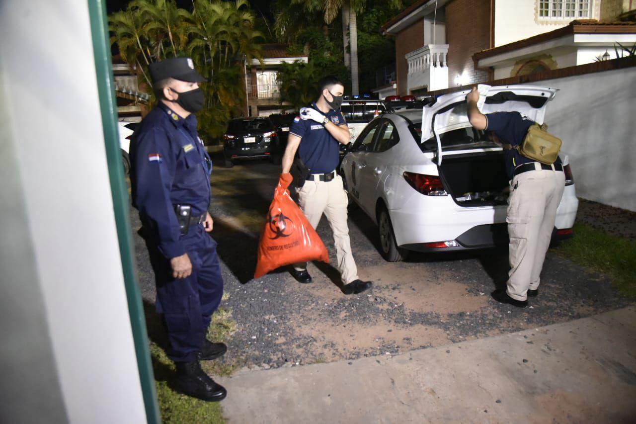 Agentes de la Policía guardan evidencias halladas en la escena del crimen.