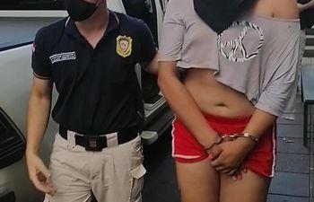 Un agente policial acompaña a la detenida.