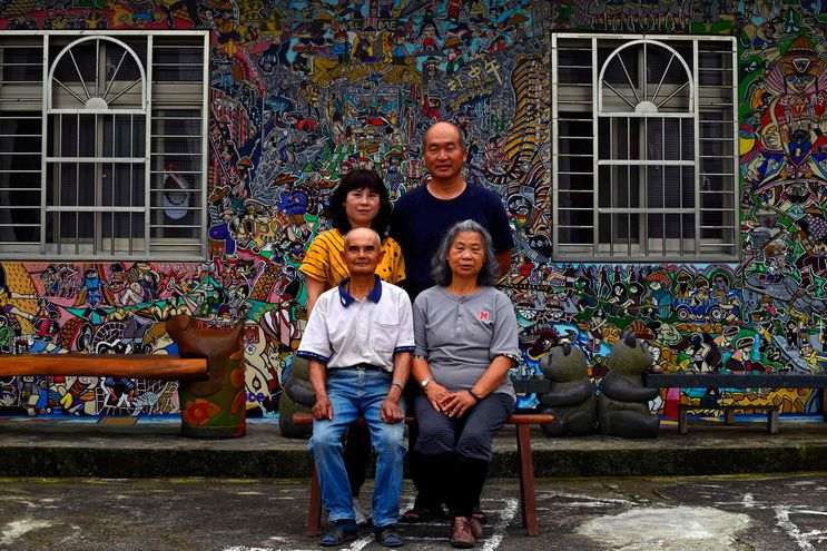 El artista de graffiti hakka Wu Tsun-hsien (arriba, der.) posando con su familia frente a su casa en el pueblo taiwanés de Ruan Chiao.
