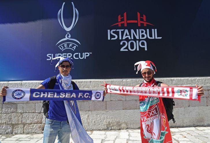 Fanáticos de ambos equipos posan con sus colores en las afueras del estadio.