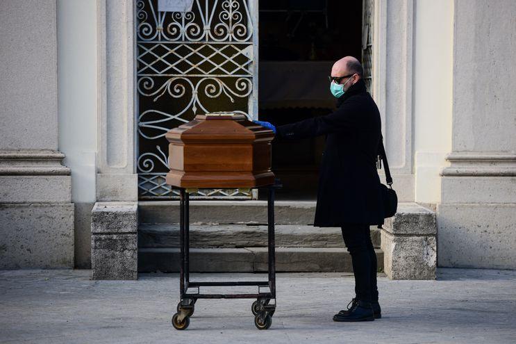 Un hombre toca el ataúd de su madre durante un servicio funerario en el cementerio cerrado de Seriate, cerca de Bérgamo, Lombardía.