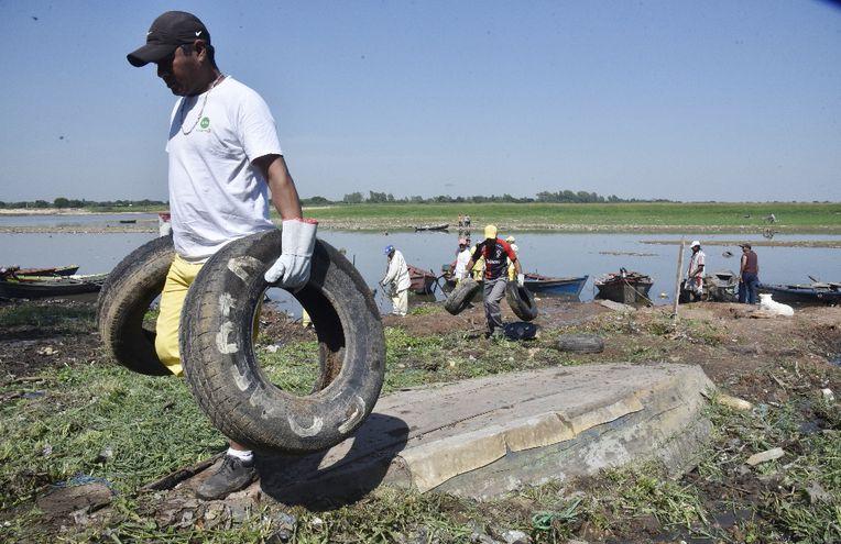 Las basuras eran tantas que flotaban en el agua, alcanzando varios metros de largo. Personas pescan y cocinan en el sitio.