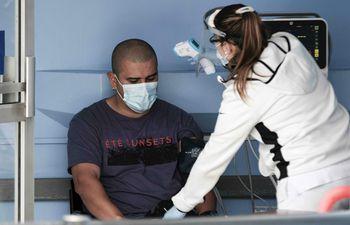 AME6594. SAN JOSÉ (COSTA RICA), 10/05/2021.- Una enfermera examina hoy a un paciente en el área de emergencias para covid-19 de un hospital, en San José (Costa Rica). Las autoridades de Costa Rica ordenaron este lunes una reducción en los aforos de algunos establecimientos comerciales como herramienta para tratar de frenar la ola de contagios de covid-19, que mantiene saturados los hospitales del país, al mismo tiempo que anunciaron una nueva compra de vacunas a Pfizer. EFE/Jeffrey Arguedas