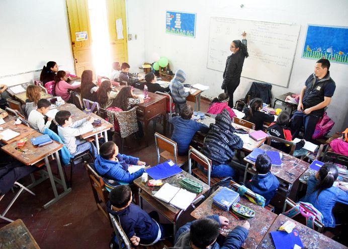 Maestra del 2° grado desarrolla su clase mientras aguarda su turno el profesor del 3°. Los alumnos se confunden todo.