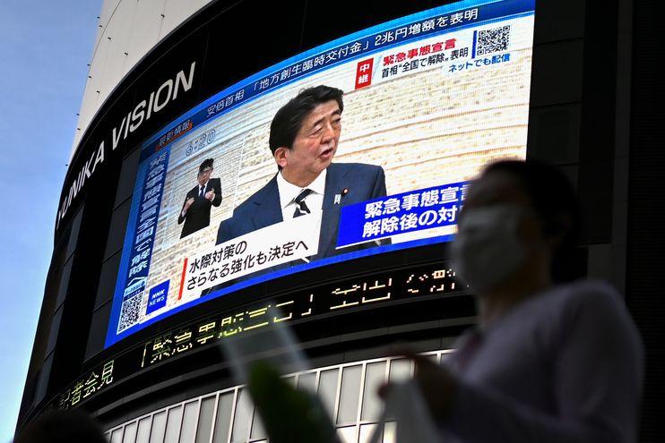 El primer ministro de Japón, Shinzo Abe (arriba), es visto en una transmisión de televisión en vivo cuando anuncia el levantamiento de un estado de emergencia a nivel nacional.