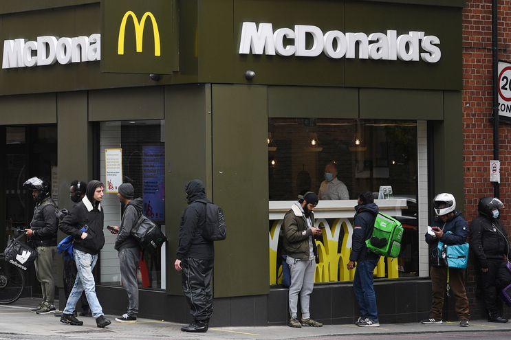 """Empleados de """"delivery"""" en fila fuera de un restaurante de McDonald's en Londres, Reino Unido."""