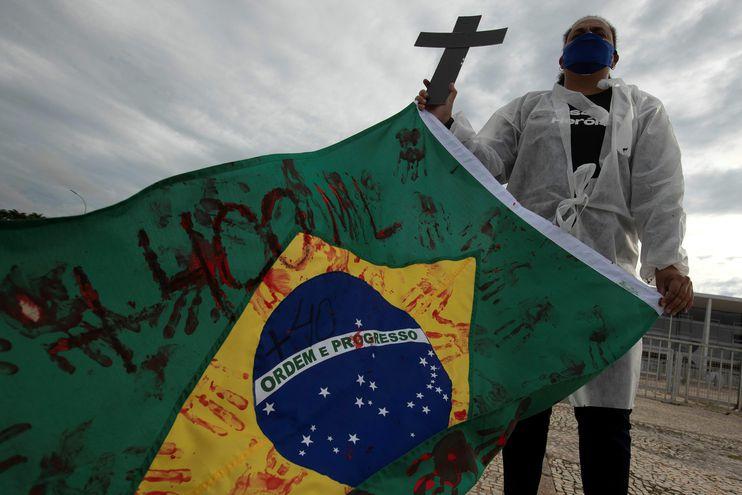 Una enfermera sostiene una bandera de Brasil en una protesta simbólica en honor a los profesionales de la salud y por las más de 400.000 muertes por coronavirus en Brasil hoy, frente al Palacio do Planalto en Brasilia (Brasil).