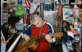 Daniel Johnston rodeado de varios de los personajes y elementos de su propio imaginario mítico y artístico en el garaje de la casa de sus padres en noviembre del 2004. Fotografía de Dan Winters.