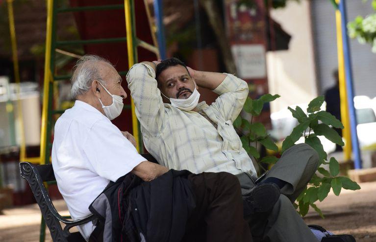 Dos personas conversan. En ambos casos el uso del tapabocas no es adecuado, ya que no cubre nariz y boca.