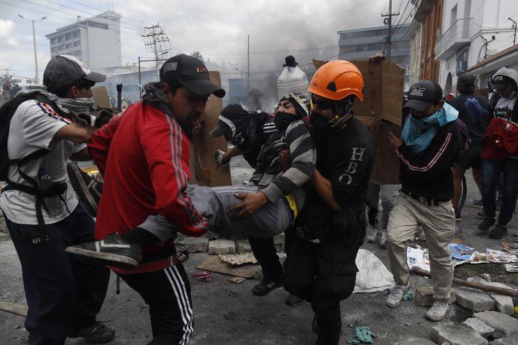 Manifestantes ayudan a un hombre afectado durante las confrontaciones con la policía cuando se cumplen 10 días de protestas contra el Gobierno este sábado, en Quito (Ecuador).