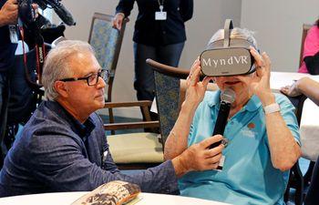 El director de salud de John Knox Village, Mark Rayner pregunta a una anciana sobre su experiencia con las gafas de realidad virtual de MyndVR.