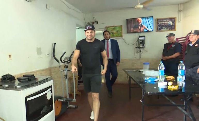 Reinaldo Javier Cabaña Santacruz, alias Cucho, camina sonriente dentro de la celda vip, durante la verificación. Detrás, Joaquín González, director de Establecimientos  Penitenciarios.