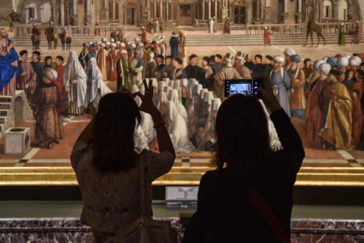Visitantes toman fotos de la pintura 'San Marcos predicando en Alejandría' de Gentile y Giovanni Bellini, exhibida en la prestigiosa galería de arte Pinacoteca di Brera en Italia.