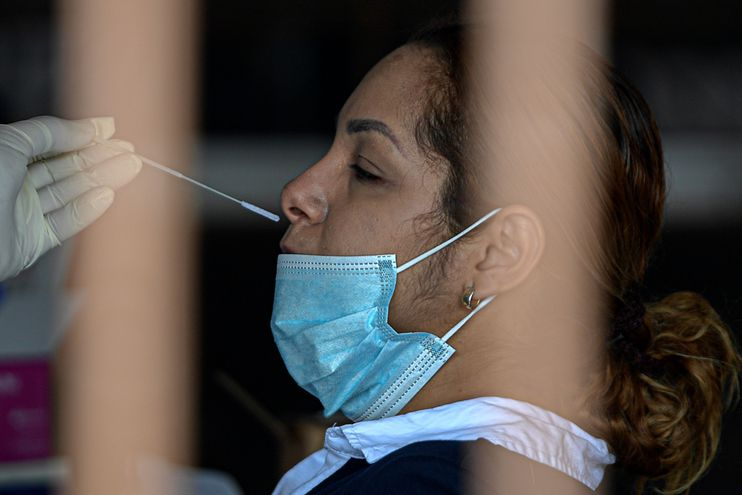 A health worker collects a nasal swab sample from a woman to be tested for COVID-19 at Las Acias neigborhood in Panama City, on July 16, 2020. - Panama exceeded 50,000 cases of COVID-19, from which some 1000 people have died. Due to an increase of contagions, the Ministry of Health announced that full quarantine will be resumed on weekends, a measure that had been lifted in early June. (Photo by Luis ACOSTA / AFP)
