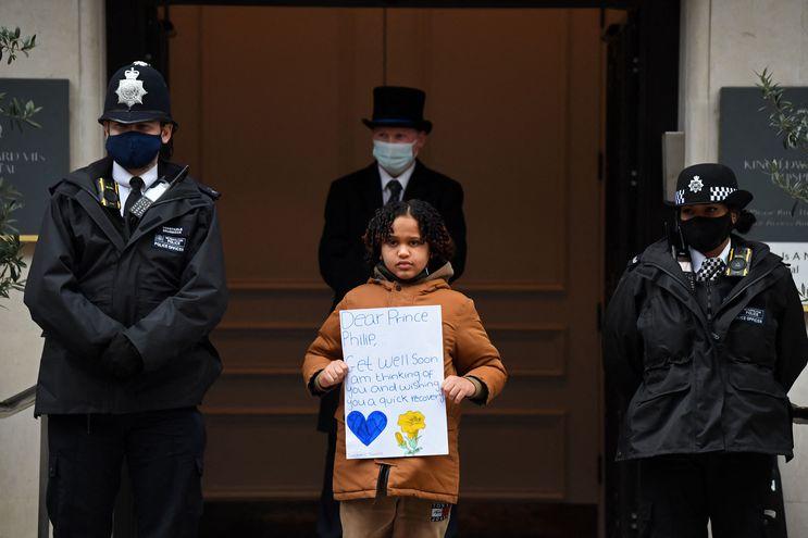Una niña sostiene un cartel deseando pronta recuperación al príncipe Felipe del Reino Unido, ante las puertas del hospital donde se encuentra ingresado desde hace una semana.