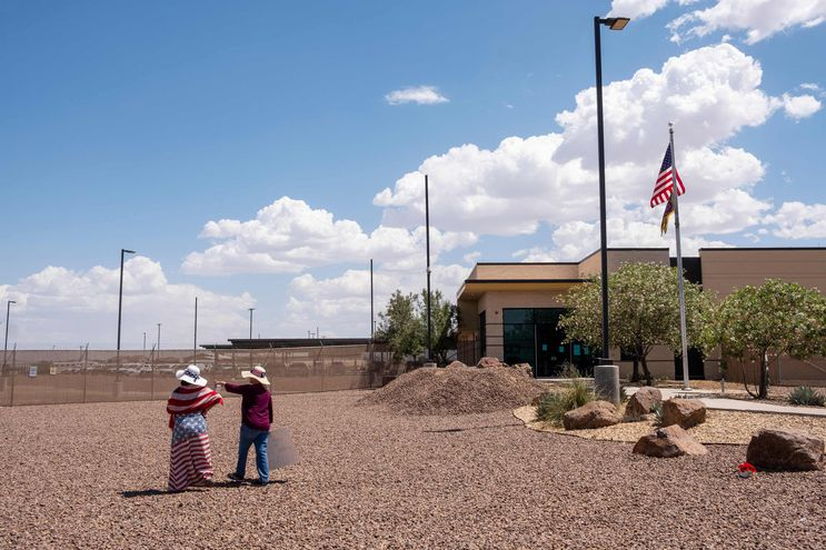 Dos personas pasan cerca de una estación de control fronterizo en Texas, EE.UU.