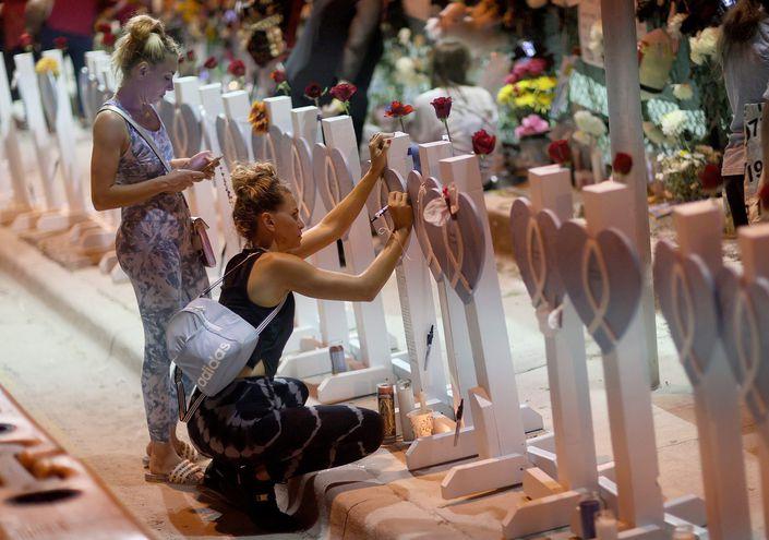 Dos mujeres visitan un memorial en homenaje a las víctimas del derrumbe del edificio Champlain Towers South en Surfside, Florida.