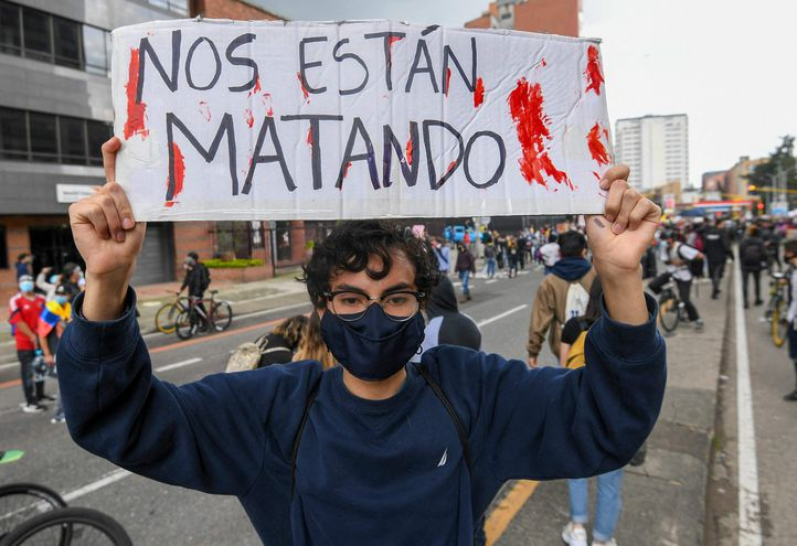 A demonstrator holds a sign reading 'They are killing us' during a protest against a tax reform proposed by Colombian President Ivan Duque's government in Bogota, on May 4, 2021. - The international community on Tuesday decried what the UN described as an 'excessive use of force' by security officers in Colombia after official data showed 19 people were killed and 846 injured during days of anti-government protests. (Photo by Juan BARRETO / AFP)
