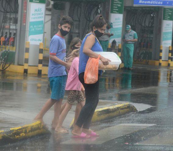 Una mujer y tres menores cruzan una calle del microcentro asunceno bajo la lluvia.